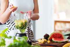 Woman preparing energetic smoothie. Woman throwing pineapple cubes into mixer with water and mint while preparing energetic smoothie royalty free stock photo