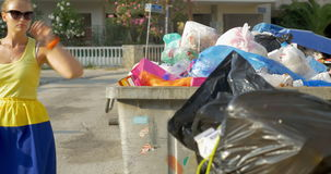 Woman throwing plastic bottle into street garbage stock footage