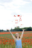 Woman throwing poppy blossoms Stock Photography