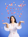Woman throwing rose petals. Lady throwing rose petals in the air royalty free stock photography