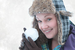 Woman throwing snow ball. Beautiful woman about to throw a snow ball with snow background Stock Images