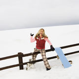 Woman throwing snowball. Young woman in winter clothes by fence in snowy field smiling while ready to throw snowball Stock Photos