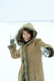 Woman throwing snowball. Woman wearing fur trimmed hooded coat throwing a snowball Royalty Free Stock Photo