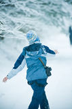 Woman throwing snowballs. A woman wearing blue winter clothes, throwing snowballs at someone royalty free stock images