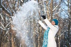 Woman throwing some snow Stock Photo