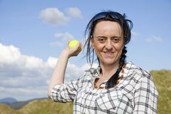 Woman throwing tennis ball. Smiling woman throwing tennis ball in sand dunes royalty free stock photos