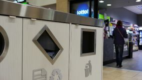 Woman throwing trash to the garbage can. Inside shopping mall stock footage