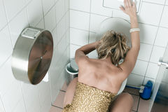 Woman throwing up in the toilet stock photos
