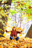 Woman throws autumn leaves in park. Royalty Free Stock Photos