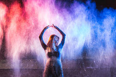 Woman throws color powder on dark background. Young beautiful woman throws color powder on dark background Royalty Free Stock Photos