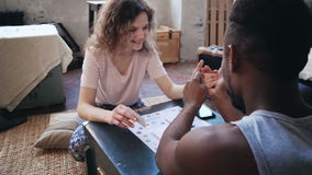Woman throws dice and takes card. Man takes her hand and draws a finger. Multiethnic couple plays the boar game. Beautiful women throws the dice and takes the royalty free stock photos