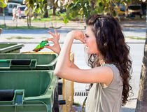 Woman throws garbage in dumpster. Woman throws garbage in a green plastic dumpster Royalty Free Stock Image