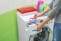 Woman throws laundry detergent into the washing machine. Royalty Free Stock Image