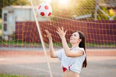 Woman throws soccer ball at stadium on background of grid of football goals stock image