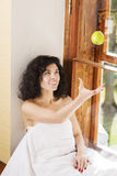 Woman throws up apple on wooden sill Royalty Free Stock Photos