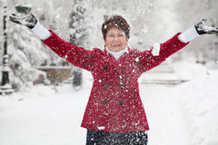 Woman throws up snow on winter snowy street Stock Photo
