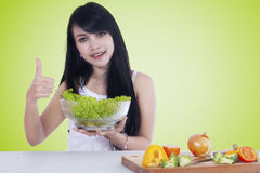 Woman with thumb up holds salad Stock Photography
