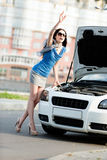 Woman thumbing a lift near the broken cabriolet Stock Photography