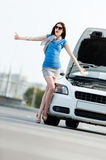 Woman thumbing a lift near the broken car Royalty Free Stock Photos