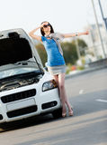 Woman thumbing a lift near the broken white car Stock Image