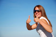 Woman with thumbs up. Attractive young woman model with long red hair, wearing sunglasses, holding her thumbs up to show her excitement about her happy holidays Stock Images