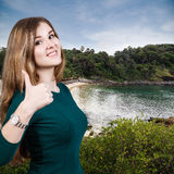 Woman with thumbs up on the beach baclground. Stock Photo