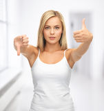 Woman with thumbs up and down Stock Photo