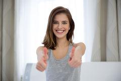 Woman with thumbs up at home Royalty Free Stock Image
