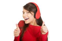 Woman with thumbs up listening to music. Stock Photography