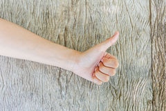 Woman thumbs up on wooden background. Royalty Free Stock Images