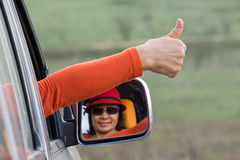 Woman thump up driving. Car mirror stock photo