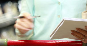 Woman ticking off grocery list. In grocery store stock footage