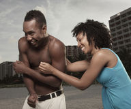 Woman tickling a man on the beach Stock Images