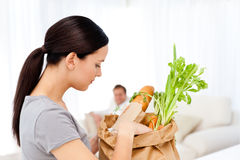 Woman tidying up the kitchen after shopping Royalty Free Stock Photography