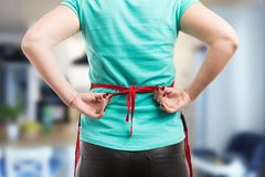 Woman tie a back knot of red apron. Getting ready to clean or cook. Close-up concept Royalty Free Stock Photo
