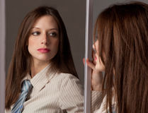 Woman in Tie Looking In Mirror. A portrait of a pretty young woman in a collared shirt and tie looking at herself in a mirror Royalty Free Stock Images
