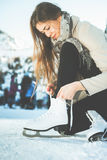 Woman tie shoelaces figure skates at ice rink close-up Stock Images