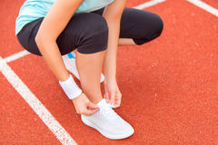 Woman tie up her shoe laces at the stadium Stock Photos