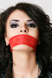 Woman with tied mouth. Woman tied mouth with red ribbon stock photography