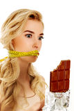 Woman with tied mouth holding bar of chocolate Stock Photo