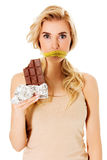 Woman with tied mouth holding bar of chocolate Stock Photos