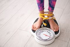 Woman Tied With Tape Measuring Her Weight Using Scales Stock Photography