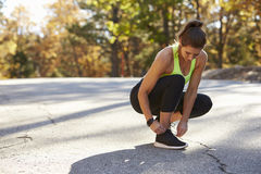 Woman ties her sports shoe before a run, looking down Stock Photos