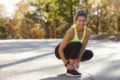 Woman ties her sports shoe before a run, looking to camera Stock Images