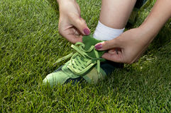 Woman ties laces on green shoes Royalty Free Stock Image