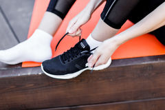 Woman ties up her shoelaces. On sneaker in gym, sitting on rug on wooden floor Royalty Free Stock Image