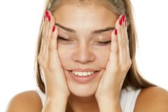 Woman tightening her face. Young smiling woman tightening her face with her hands Royalty Free Stock Images