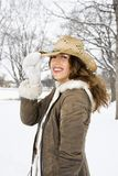 Woman tilting cowboy hat. Caucasian young adult female smiling and tilting straw cowboy hat at viewer Royalty Free Stock Photography
