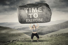 Woman with time to exercise word on stone Royalty Free Stock Image