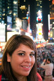 Woman In Times Square NYC. A young woman smiling as she stands in Times Square in New York City stock images